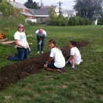 Brittany working in a garden for Reach Out Saint Rose.