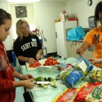 Saint Rose students, Alcyia Little, Kelly Slingerland, and Megan Evans help prepare a salad for a ziti dinner.