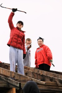 Meghan (left) with two other students on top of Errol's roof. Throughout the week students worked to remove rotten boards to rebuild the frame of the home.