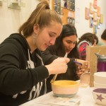 Kate F., the Interfaith Sanctuary GA painting bowls for the annual 'Fill Their Bowls' Mac 'n Cheese Cookoff held during Social Justice Week.