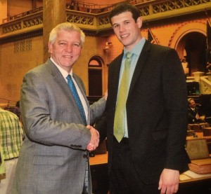 (Caption) From Saint Rose intern to legislative aide: Assembly member Kevin Cahill, D-103, greets Saint Rose intern Vincent Rossetti '14 in the Assembly chamber just prior to a recent legislative mock session. The next time the legislative body takes to the floor, Rossetti will be there as a member of Cahill's staff.