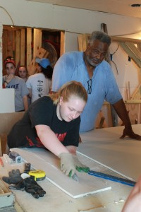 Errol Joseph, homeowner, oversees Sheetrock measurements done by Paige.