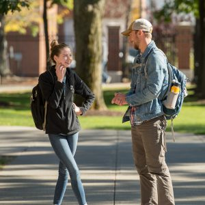 two students talking to each other on the campus green