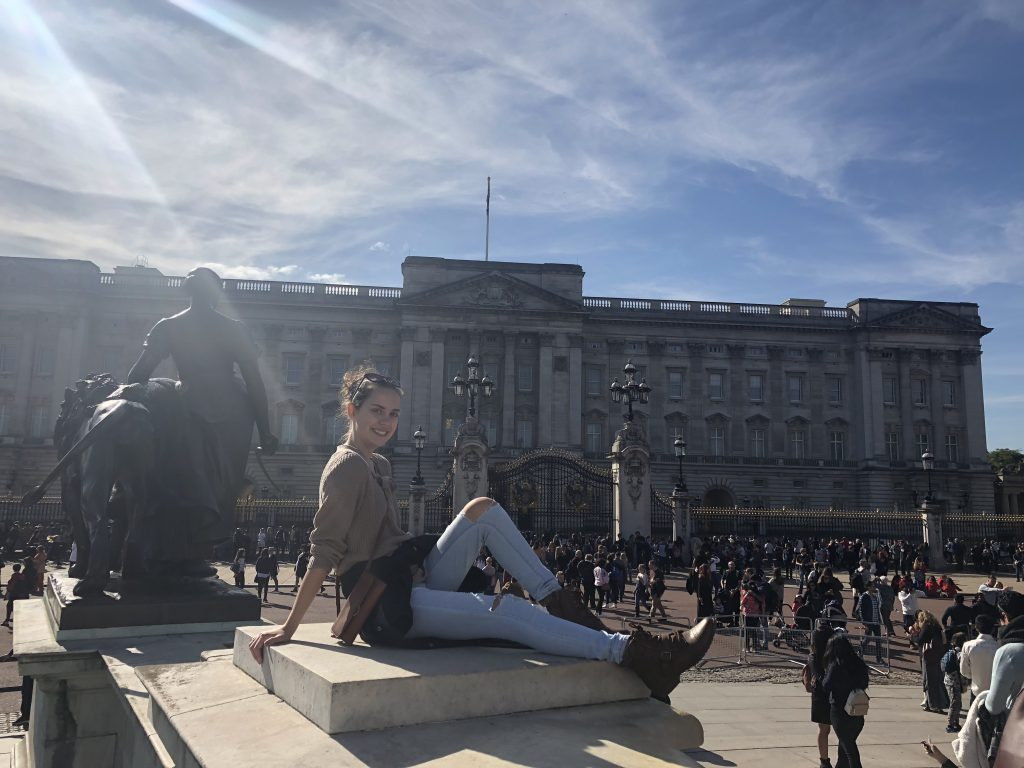 Saint Rose student sitting in front of Buckingham Palace