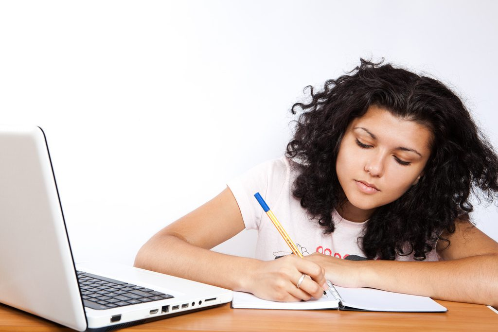 woman writing in notebook while sitting near open laptop