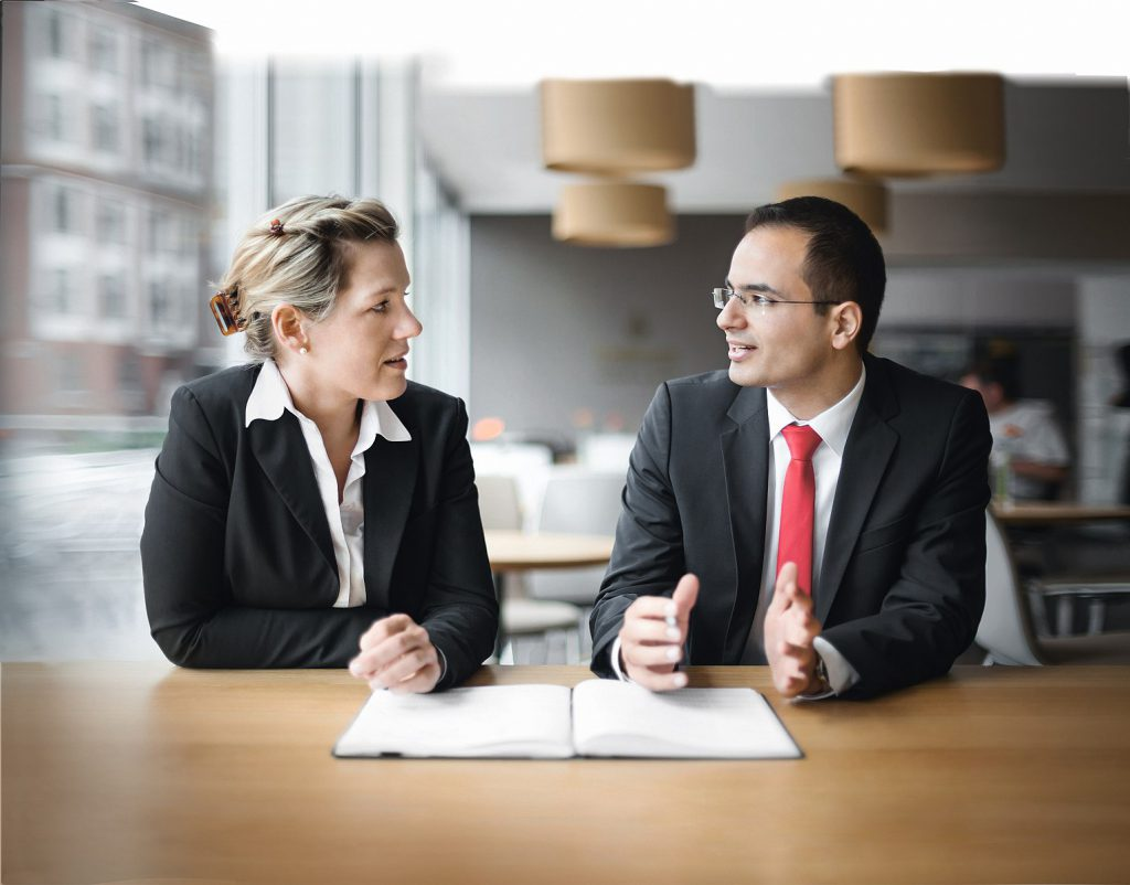 man and woman meeting sitting side by side at a desk