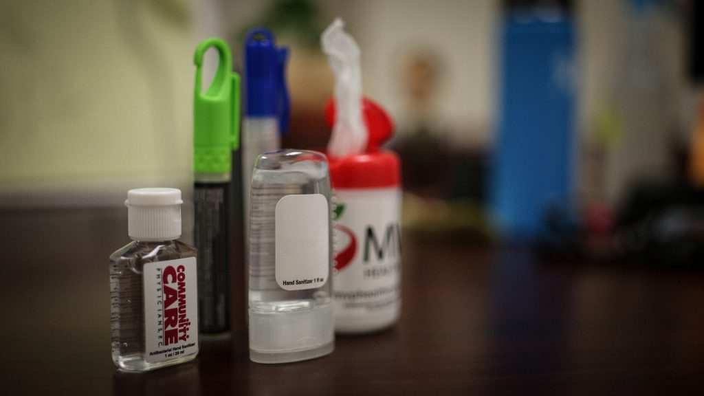 an assortment of hand sanitizers sitting on a desk