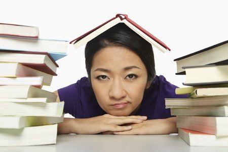 woman sitting under a book with books around her, showing reluctance to study