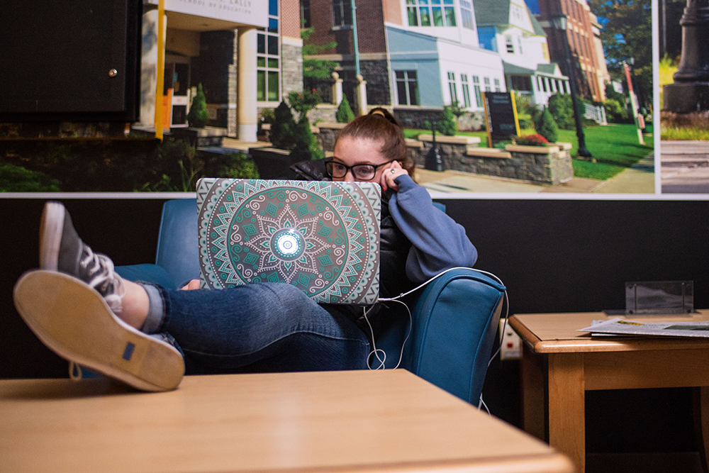 student sitting in commuter lounge on her laptop