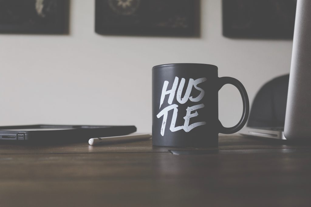"A coffee mug next to a laptop that says ""hustle"""