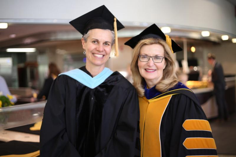 Professor Drey Martone with Saint Rose President Carolyn J. Stefanco, both in graduation attire, after the 2019 commencement ceremony.