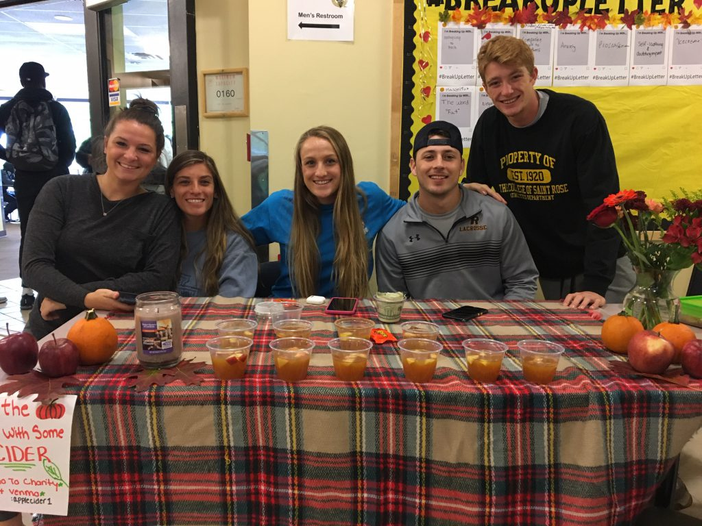 A group of students selling apple cider