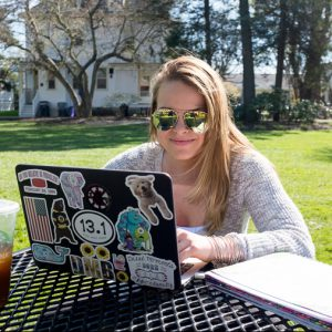 Female Saint Rose student sitting with computer outside.