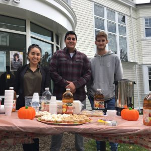 students outside of Huether School of Business selling apple cider