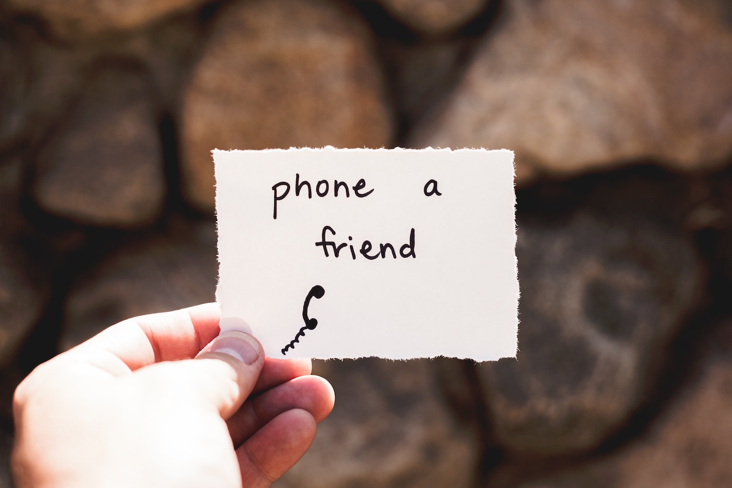 hand holding paper that reads phone a friend