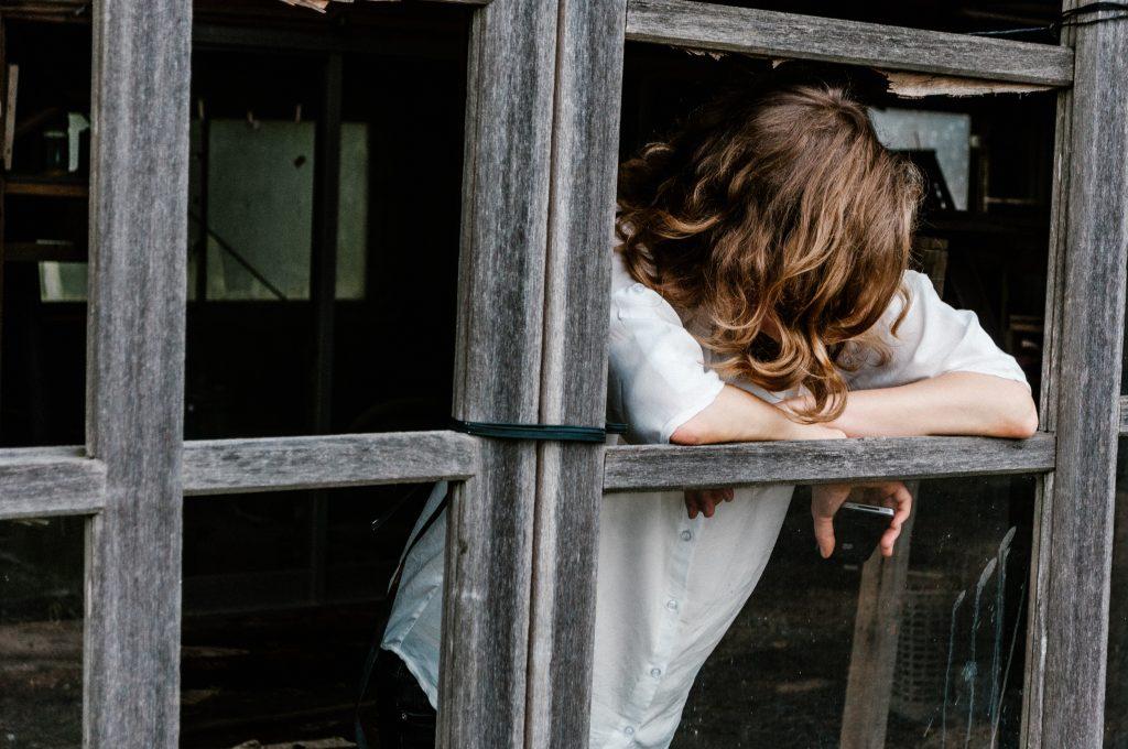 sad teenager leaning on window frame