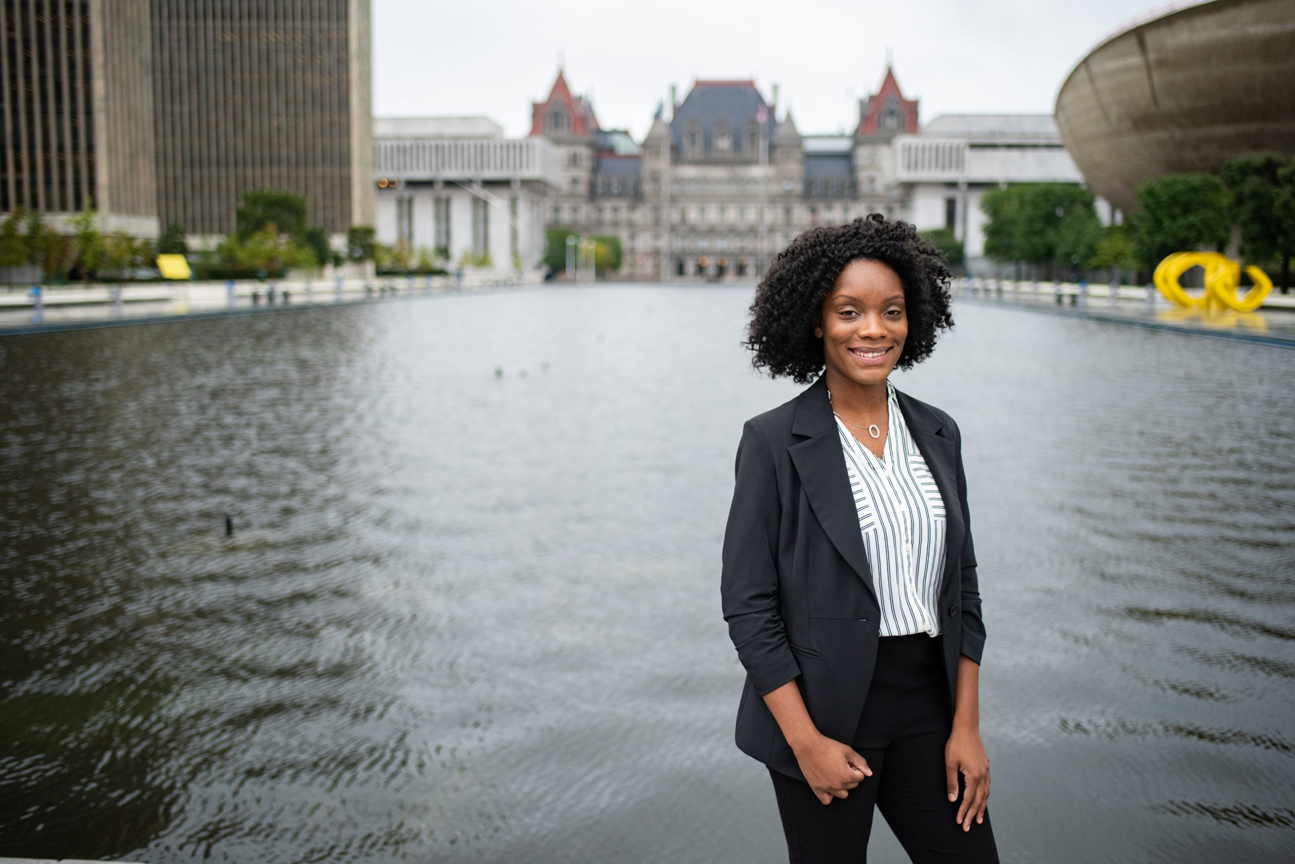 College student standing in front of the NY State Capital Building
